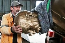 Zaměstnanec technických služeb drží hlavu T. G. Masaryka při pokládání sochy ve skladu ve Velebudicích.