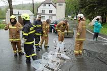 Hasiči z Nové Vsi pomáhají v Českém Jiřetíně odklonit vodu, aby nezatopila rodinný dům.