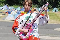 Fanda v dresu hraje na nafukovací kytaru. Za ním vyrostlo na Loučkách stanové městečko. Příznivci hokeje mají sraz v Litvínově.