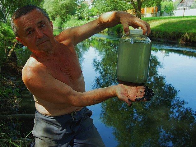Voda ve sklenici je voda, kterou Zapletal odebral z řeky ve čtvrtek. V pátek již byl vidět hustý černý kal na dně a mastná páchnoucí tmavá voda.