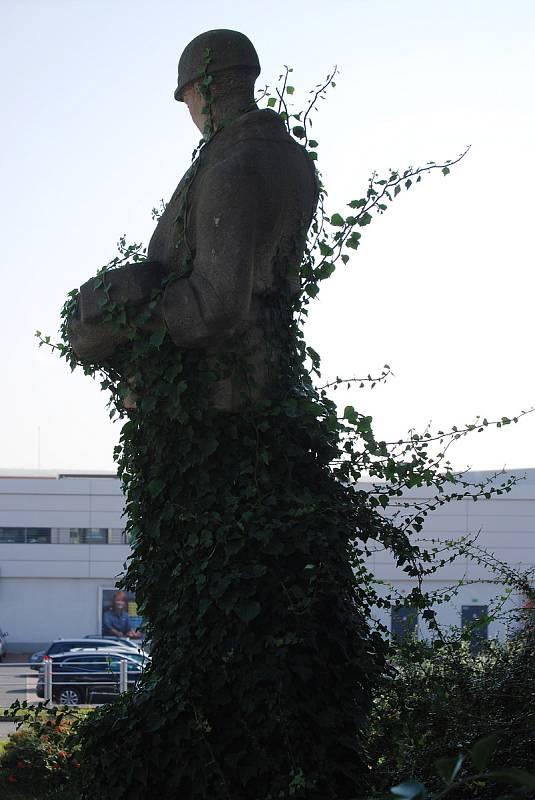 Zarostlá socha horníka u Kahanu v Mostě.