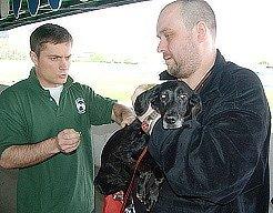 Veterinář Petr Vaculín (vlevo) očkuje psa proti vzteklině.