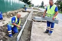 Josef Stecker (vlevo) a Josef Repka pracují na novém chodníku v Podbořanech u plotu bývalých kasáren. V pozadí Ladislav Kruml.