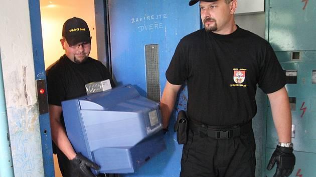 Městští strážníci zabavují dlužníkům majetek.