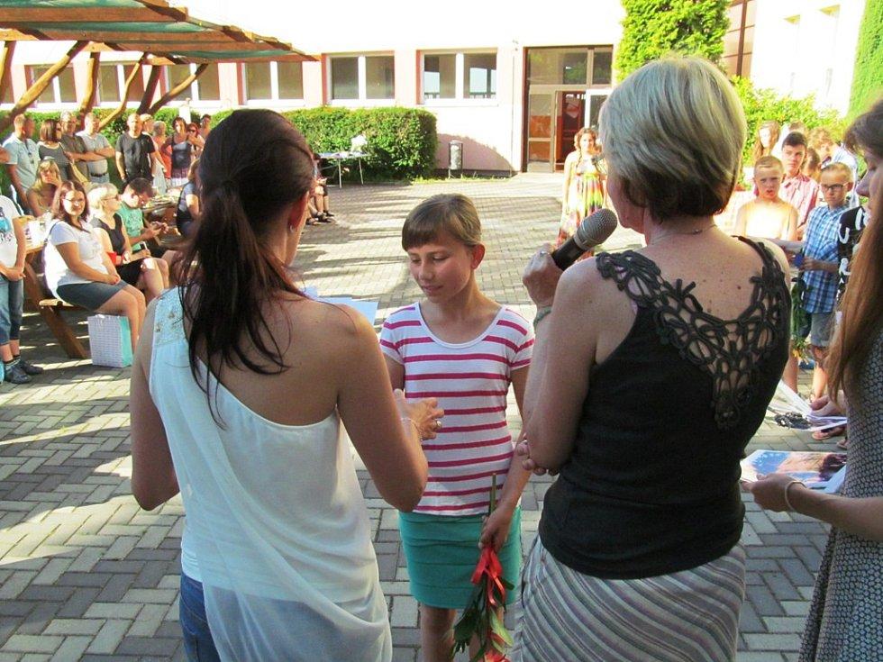 Páťáci dostali vysvědčení na dvorku. Byli u toho i jejich rodiče.