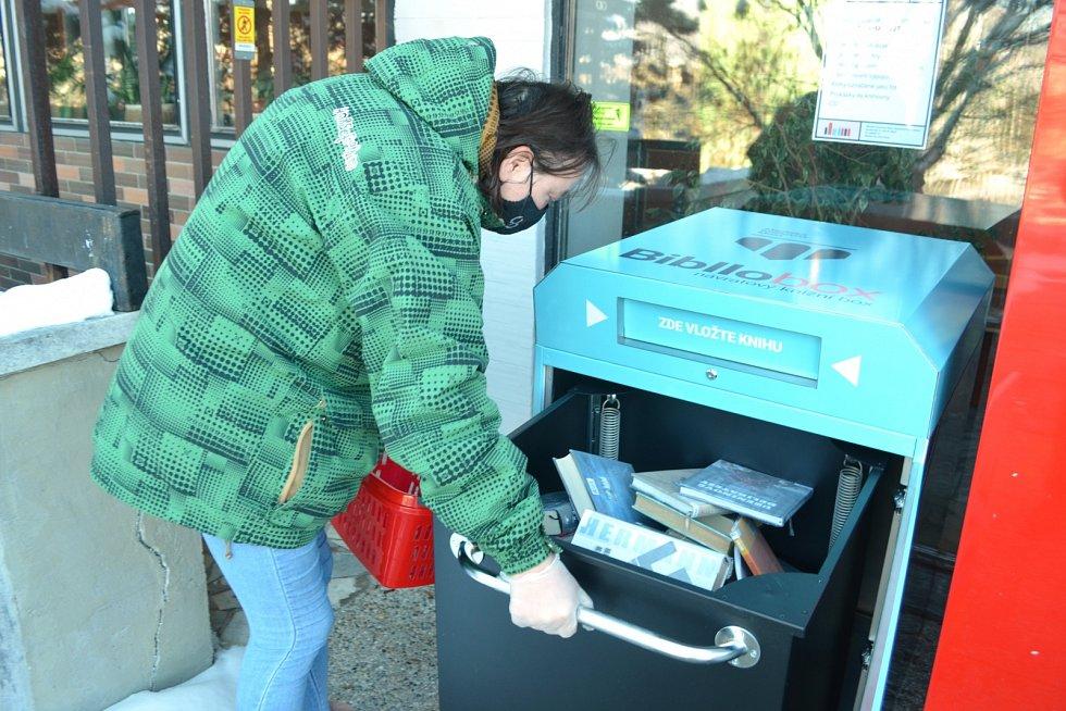Knihovnice Jitka Jílková vybírá vrácené knihy z knihoboxu u Městské knihovny v Mostě