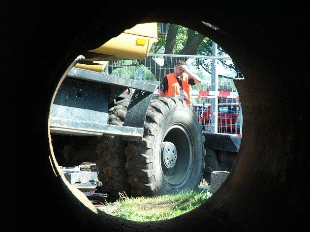 Potrubář si v Mostě v úterý ráno utírá pot z čela u obří  zrezivělé horkovodní roury vytažené z jámy.