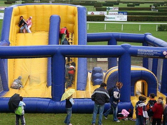 Děti si užívají legrace na skákacím hradě.