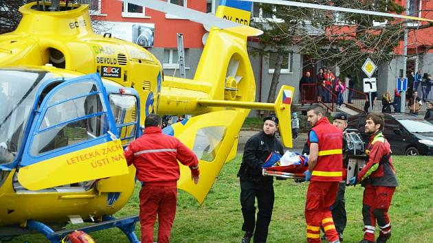 Policisté a zdravotníci nakládají do vrtulníku opařené dítě na nosítkách.