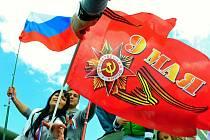 Členové místní ruské komunity vztyčují své vlajky na tanku sovětské výroby při mostecké oslavě 70. výročí konce 2. světové války.