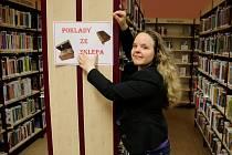Vedoucí dospělého oddělení Michaela Hrabinská umisťuje ceduli lákající na jednu z novinek Poklady ze sklepa.