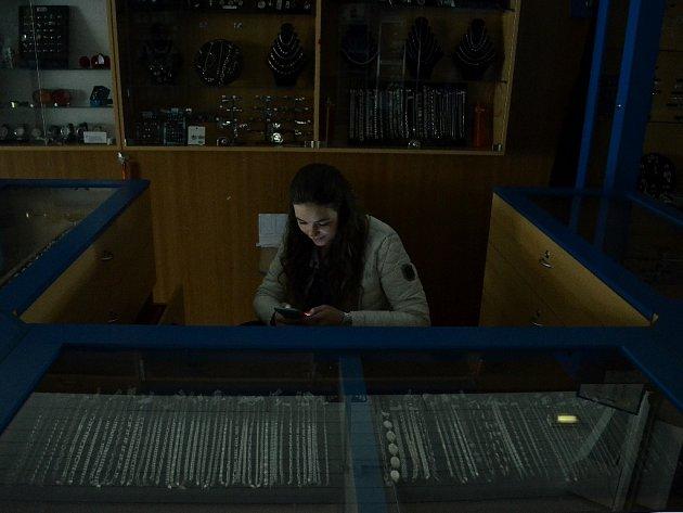 Prodavačka si krátí volnou chvíli v potemnělém Prioru při výpadku elektřiny.
