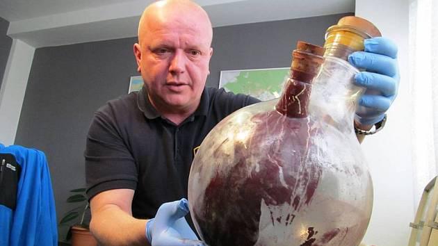 U drog se počet skutků zvýšil. Na snímku mostecký policista s věcmi z laboratoře na výrobu drog.