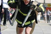 Hasič musí pořádně zabrat, aby hadice roztáhl, na zádech má ještě čtrnáctikilový dýchací přístroj.
