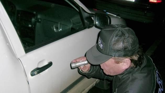 Strážník ohledává poškozené vozidlo.