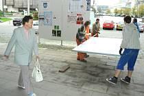 Lidé z technických služeb sundavají městský panel, kde se mohly strany lepit zdarma.