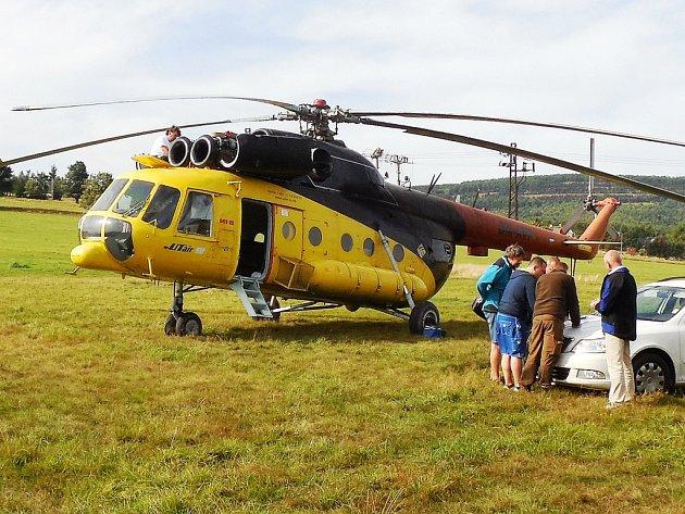 Vrtulník k vápnění lesů stojí na hřišti v Nové Vsi v Horách, kde odborníci studují mapy.