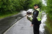 Strážník usměrňuje provoz na silnici u Mariánských Radčic, která byla v pondělí zaplavená.