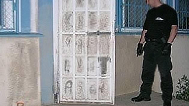 Strážník u poškozených dveří školky, která byla vykradena.