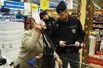 Policista radí v Albertovi v Centralu seniorce, aby neměla kabelku s penězi ve vozíku.