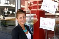 Kateřina Bartková si prohlíží výlohu prodejny s módním zbožím. Výhodně si v rámci výprodeje pořídila například sako.