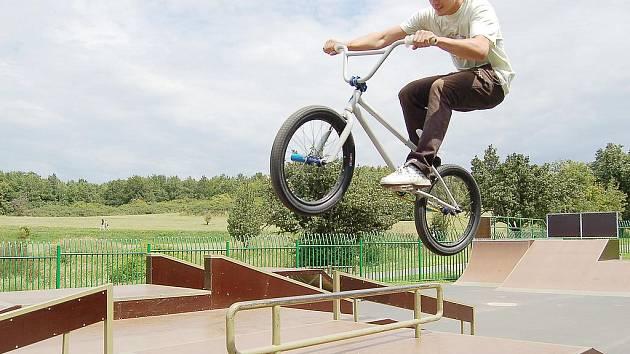 Mladý jezdec dovádí na kole v mosteckém skateparku.