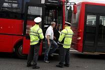 Policisté kontrolují řidiče autobusu.