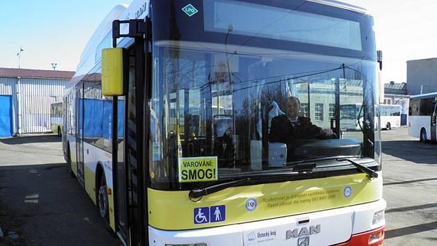 Pozor smog, varuje cedulka za oknem autobusu.