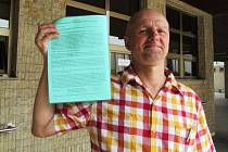 Předseda petičního výboru Josef Fiala s peticí v ruce před budovou magistrátu.