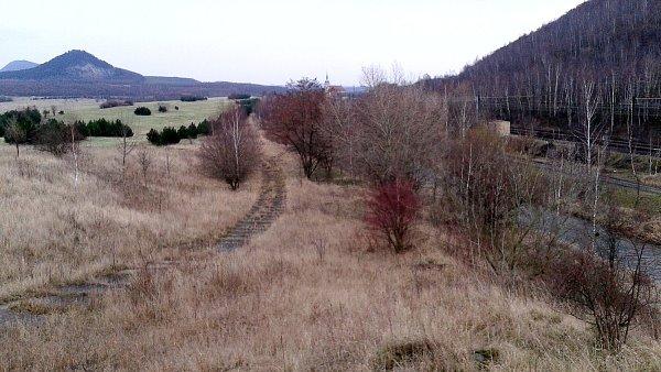 Tudy povede silnice. Vpravo je úpatí vrchu Hněvín sdopravním koridorem a řekou Bílinou, vdáli uprostřed je kostel a vlevo území sjezerem.