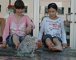 Tereza Uličná a Nikola Šatrová si chladí nohy v kašně na mosteckém náměstí.
