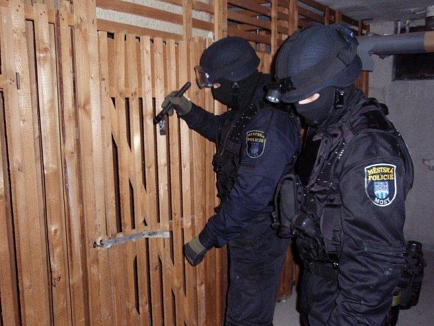 Mostečtí strážníci při prohlídce rizikových domů v tamních sídlištích.