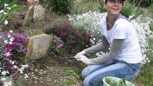 Zaměstnankyně komořanské teplárny pomáhá na zahradě obecně prospěšné společnosti Energie.
