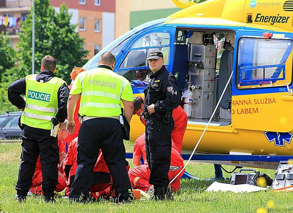 Záchranáři ošetřují zraněného chodce při páteční nehodě u mosteckého Kahanu.