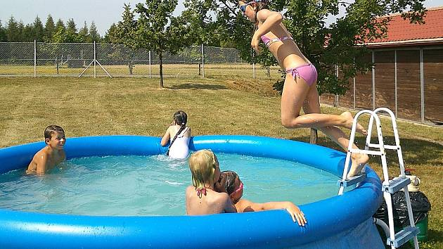 Děti dovádějí v bazénu na příměstském táboře v areálu mosteckého hipodromu, kde se učí rozumět koním.