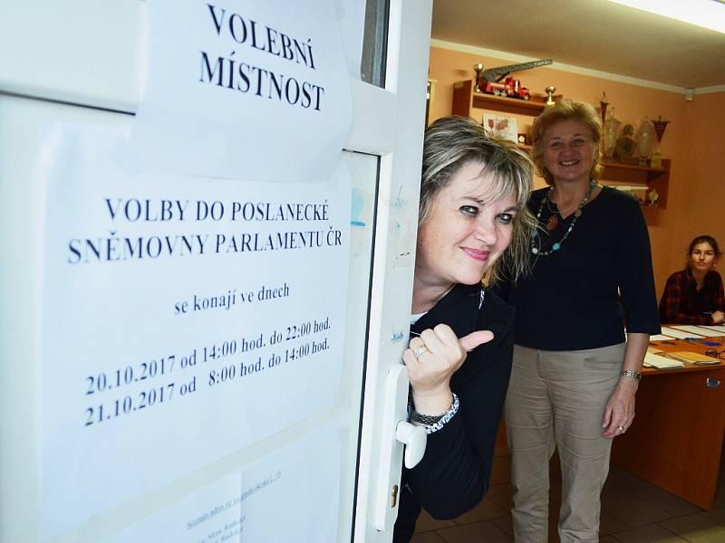 Volby v Mostě v pátek 20. října. Předsedkyně okrskové volební komise v Rudolicích Olga Zrostlíková vykukuje z hasičské zbrojnice, kde se hlasuje. Za ní stojí Dana Reinerová. Mezi členy komise panuje veselá nálada.