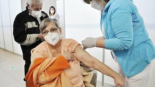 Zdravotní sestra Martina Kratochvílová očkuje Růženu Cífkovou ve velkokapacitním očkovacím centru v tělocvičně Sportovní haly v Mostě.