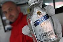 Záchranář drží v ruce zajištěnou placatku vodky