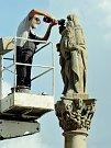 Restaurátor opravuje sochu sv. Anny Samotřetí na barokním sloupu na 1. náměstí v Mostě