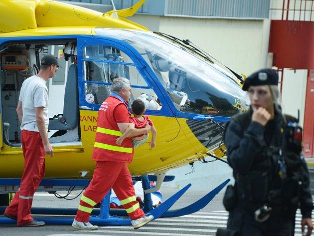 Záchranář nese přiotráveného chlapce u helikoptéry.