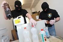 Policisté se zabavenými věcmi na výrobu drog.