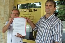 Ivan Dlouhý a Martin Martinovský ukazují u radnice petici. Ta v rušném městě myslí na uši a nervy obyvatel.