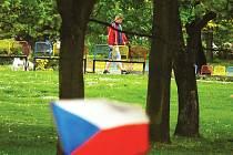 Muž se psem kráčí parkem u sportovní haly.
