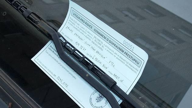 Parkovačka, která řidiči v Mostě sděluje, že do pěti dnů musí zaplatit pokutu za přestupek. Tento lístek nahradí botičky.