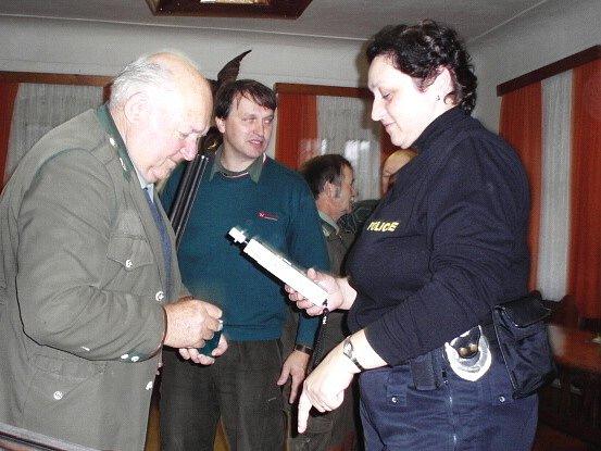 Policistka provádí dechovou zkoušku u jednoho z myslivců.