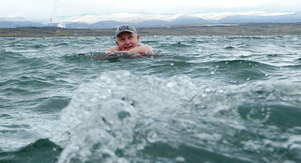 Otužilec Jindřich Bednařík z Mostu si vychutnává studenou koupel ve vlnách jezera Most v pátek 25. prosince