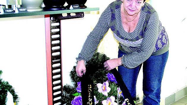 Valerie Komedová připevňuje stuhu na věnec. Většina lidí si objednává k obřadu věnce a kytice z živých květin, vkusné ale jsou i naaranžované umělé věnce. Při vypravování pohřebních obřadů mají pozůstalí výběr z široké škály.
