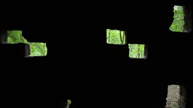 Otvory ve zdevastované bývalé promítací kabině s výhledem do lesa, kterým zarostl amfiteátr na Resslu v Mostě.