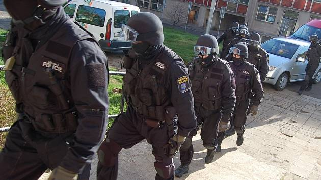 Mostečtí strážníci se připravují k zásahu proti narkomanům, kteří mají neoprávněně obývat jeden z prázdných bytů.