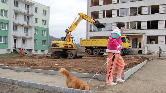"""Žena venčí psa v opravované spodní části sídliště. Podobně teď vypadá celý Chánov. Obyvatelé změny vítají. Chtěli by opravit nebo zbourat zbylé rozkradené a zdemolované paneláky, kde už žít nechtějí. """"Nic jiného jim ale nezbývá,"""" řekla jedna z žen."""